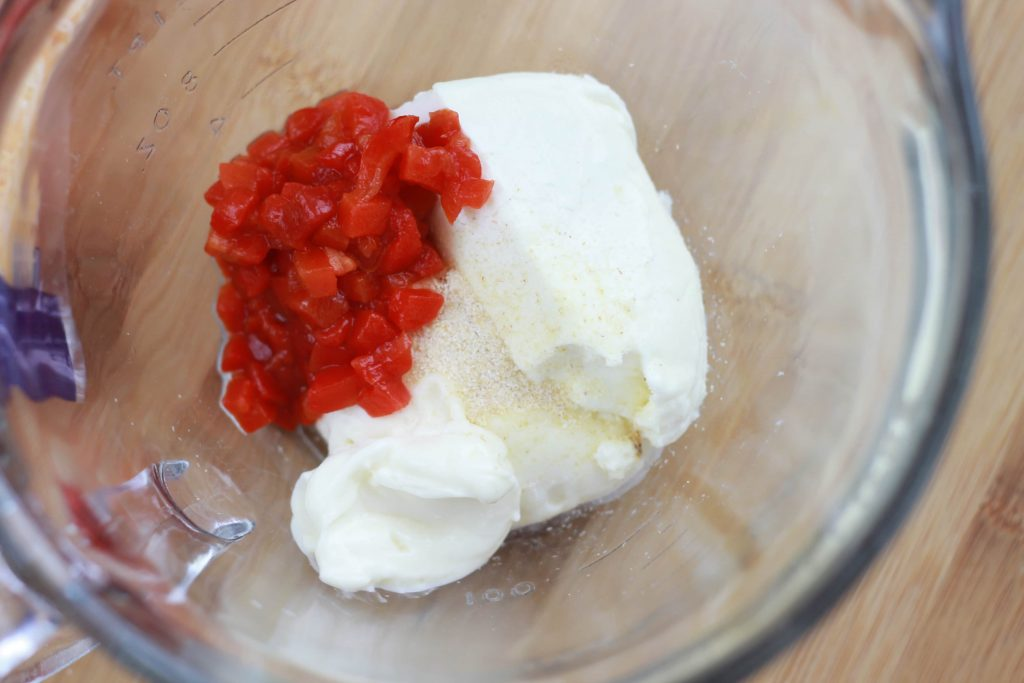 Cream cheese and diced red tomatoes in a clear mixing bowl.