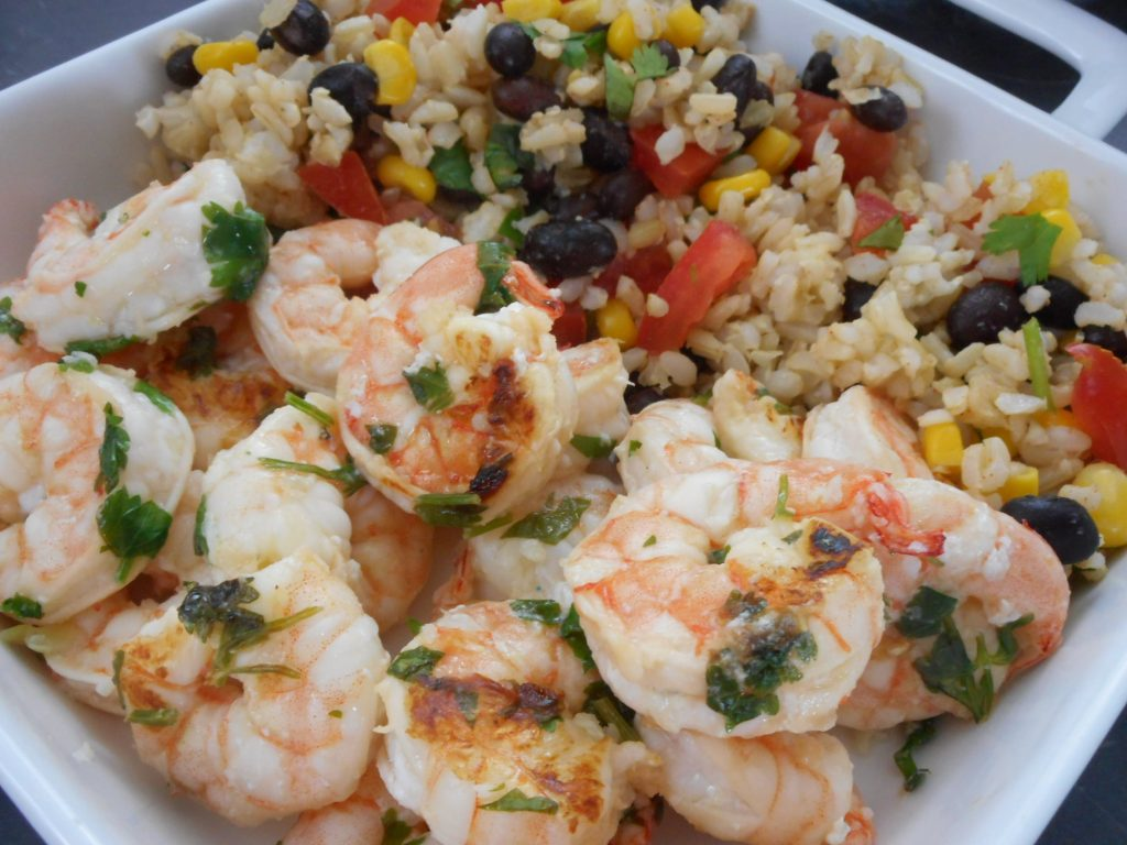 Cilantro lime shrimp, served with a side of brown rice and black beans on a white plate.