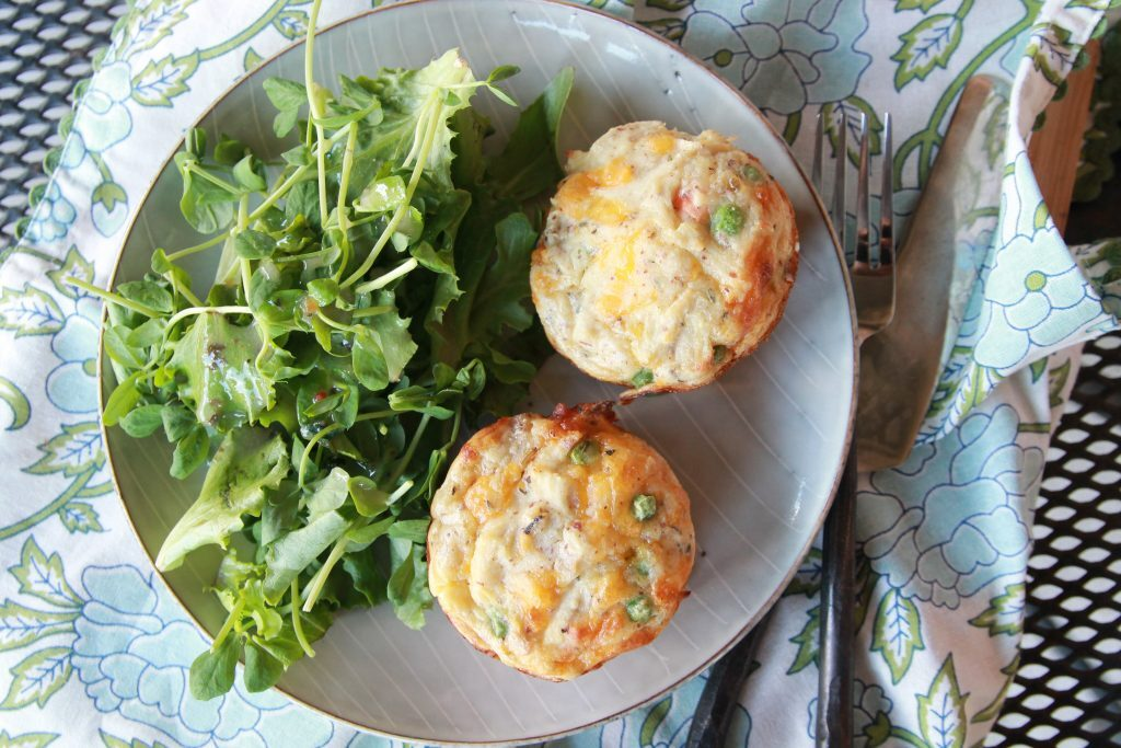 mini chicken pot pie biscuits with green salad on a round plate with fork and knife.