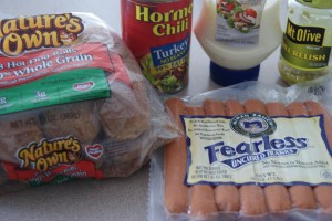 A package of whole grain hot dog buns, a package of hot dogs, a can of chili, a bottle of mayo and jar of pickles all placed on a counter ready to be prepped.