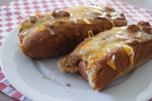 Two chili cheese coney hot dogs, topped with shredded cheese, served on a white plate.