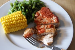 Slow cooked pork chops topped with chili sauce, served with a side of green beans a petite ear of corn, all served on a white plate.