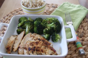 Lemon grilled dill chicken, served on a plate with a side of broccoli and a side cup of brown rice.