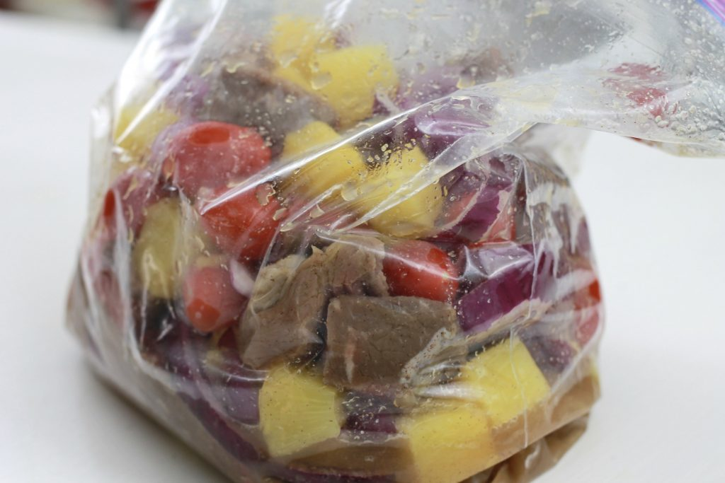 Beef, allspice seasoning, chopped red onion, pinnacle chunks, 5th seasoning, and red petite tomatoes all mixed together in a plastic bag.