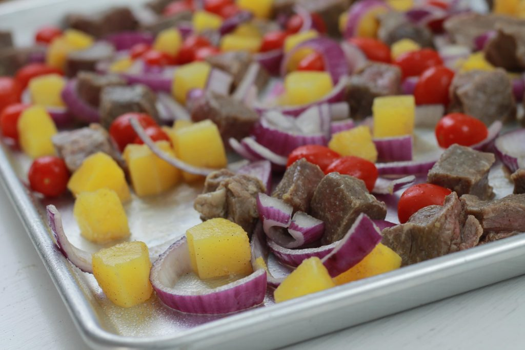 Beef, allspice seasoning, chopped red onion, pinnacle chunks, 5th seasoning, and red petite tomatoes all speed out on a baking sheet ready to be cooked in the oven.
