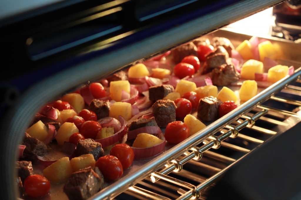 Beef, allspice seasoning, chopped red onion, pinnacle chunks, 5th seasoning, and red petite tomatoes in the oven cooking on a baking sheet pan.