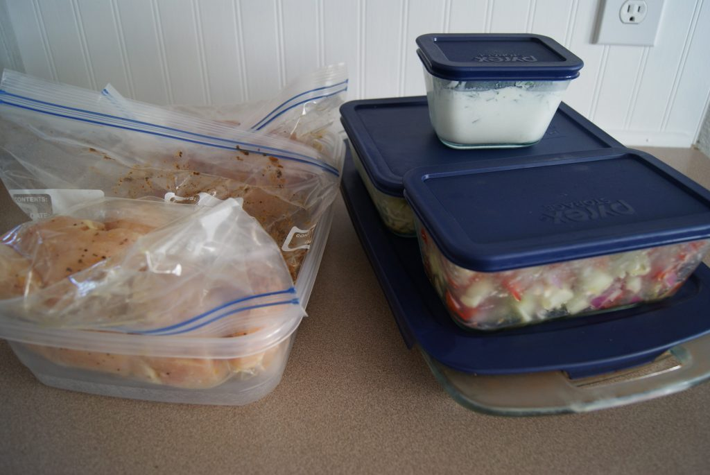Prepped meals in glass storage containers ready to be stored, along side a plastic container with prepped meals in plastic zip lock baggies on a counter.