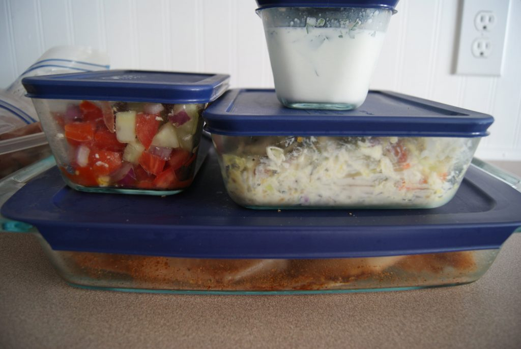 Prepped meals in glass storage containers ready to be stored.