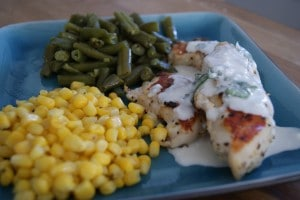 Cilantro cream chicken tenders served on a blue plate with a side of corn and green beans.