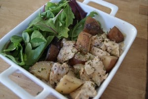 Slow cooked creamy turkey and potatoes served in a white dish with a side salad.