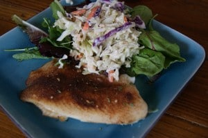 Blackened Tilapia served on a blue plate with a side salad topped with coleslaw.