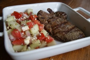 Greek grilled steak in a white dish served with a side of cucumber and petite tomato salad.