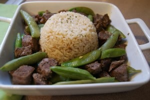 Slow cooked Asian spiced beef served with edamame and brown rice on a white dish.