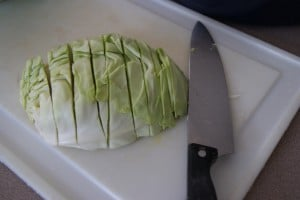 Sliced cabbage on a white cutting board with a knife.