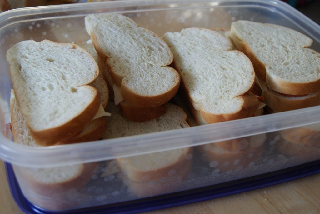 French bread sandwiches with pepperoni and provolone cheese in a container.