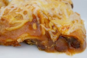 Bean and cheese enchilada topped with shredded cheese served on a plate.