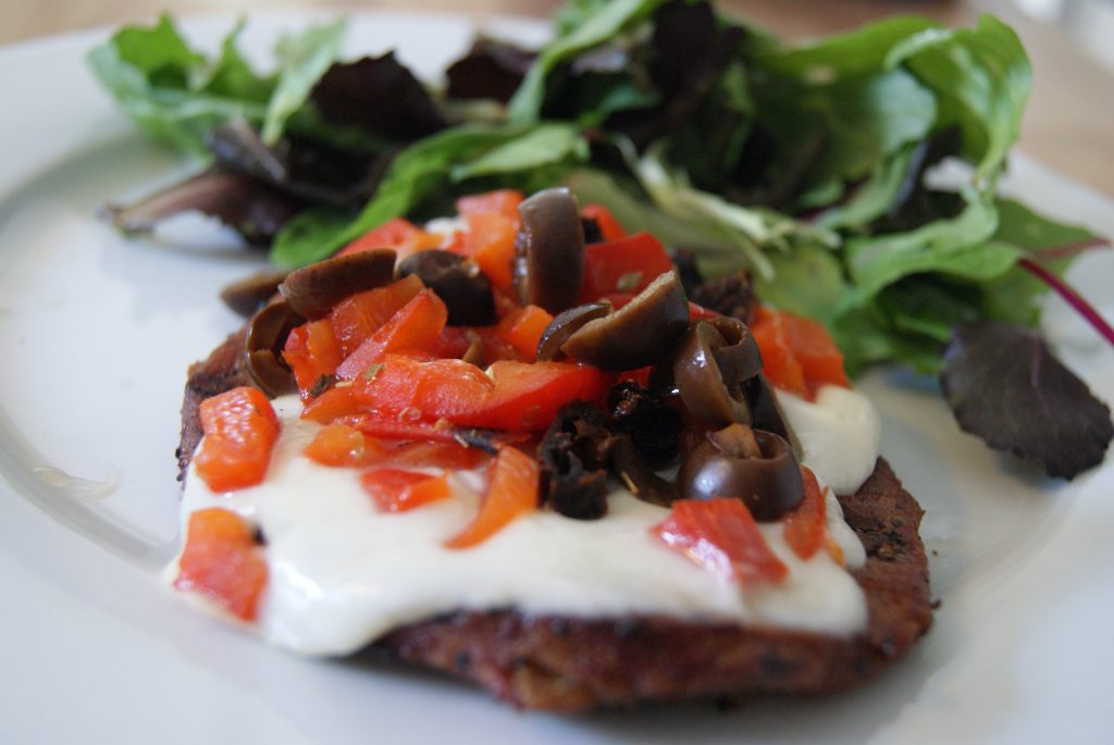 A burger patty topped with melted cheese, diced tomatoes, and sliced olives, on a plate with a side salad.