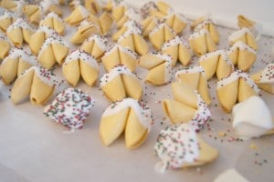 Many white chocolate covered fortune cookies placed on a baking sheet.