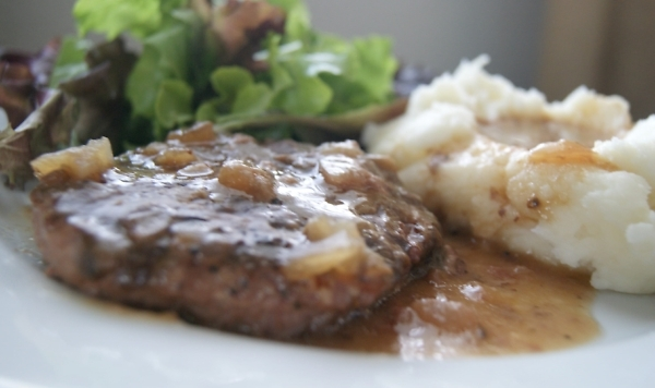 Salisbury steak with a brown mushroom gravy served with mashed potatoes and green salad on a white plate.