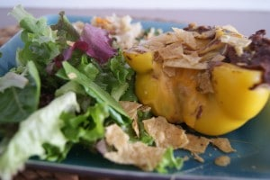 Yellow bell pepper stuffed with refried beans and covered with cheese. Served with a green salad on a blue dish.