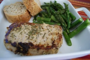 One pork chop seasoned with herbs and served on a white plate with a side of asparagus and two slices of bread.