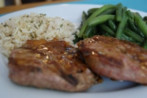 Grilled orange glazed turkey patties served with rice and green beans on a white plate