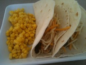 Two BBQ chicken tacos topped with shredded cheese and a side of corn on a white plate.