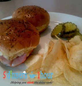 Two baked ham and cheese sliders with a side of potato chips and pickles, served on a white plate.