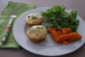 Two mini chicken pot pie cups served on a plate with a side of carrots and side salad.