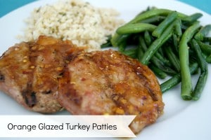 orange glazed turkey patties on a white dish, served with green beans and rice.