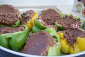 Green and yellow bell peppers stuffed with refried beans in a baking dish.