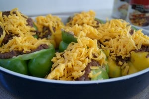 Bell peppers stuffed with refried beans and covered with cheese in a baking dish.