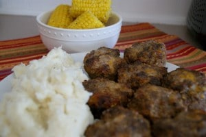 Honey Meatloaf served with a side of mashed potatoes and a bowl of petite ears of corn.