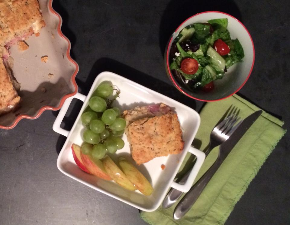 An oven baked sandwich served on a plate with grapes and apple slices, with a side salad.