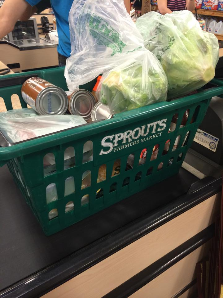 A Sprouts shopping basket filled with groceries, including, a head of lettuce, a head of broccoli, cans of beans and packages of meat.