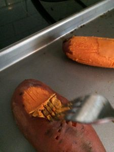 oven roasted sweet potato being sliced with a fork.