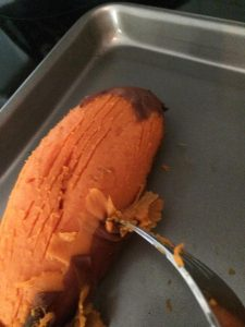 Oven roasted sweet potato being peeled by a fork.