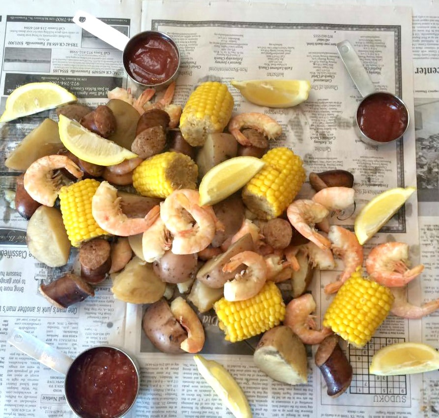Shrimp, corn cobs, potaotes and lemon wedges dumped on a sheet of news paper. With cocktail sauce in measuring cups for dipping.