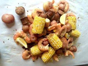 shrimp boiled on sheet paper with corn on the cob, potatoes and sausage.
