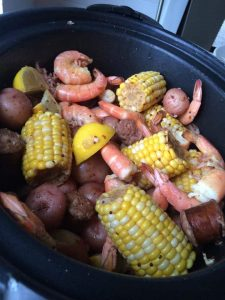 Shirmp, corn on the cob, potatoes and sausage in a crock pot for a shrimp boil.