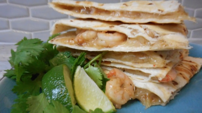 A stack of shrimp quesadillas with melted cheese and a side of two limes and cilantro.