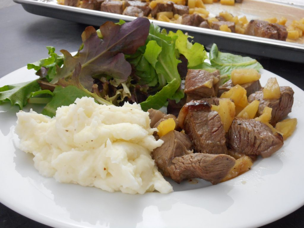 Steak bites and pineapple served with a side salad and a side of mashed potatoes on a white plate.
