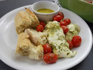 Chicken topped with pesto, petite tomatoes, and bread with a side of butter served on a plate.