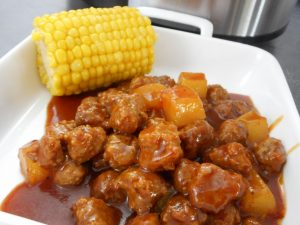 Slow cooked meatballs covered in BBQ sauce served with a petite ear of corn on a white plate.