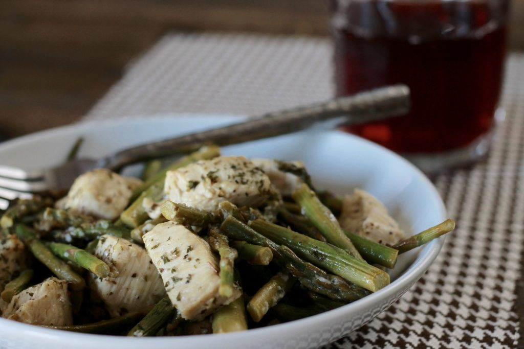 Seasoned slow roasted chicken, with asparagus bites served in a white bowl.