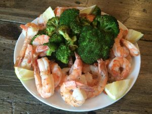 Shrimp, topped with broccoli and served with a sliced lemon on a plate.