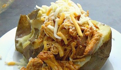 Shredded BBQ chicken, on top of a baked potato topped with shredded cheese.