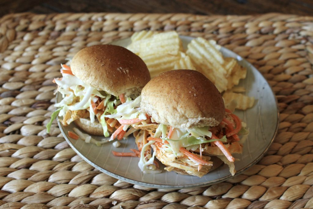 Two Buffalo chicken sliders with lettuce and sliced carrots served with a side of potato chips on a plate.