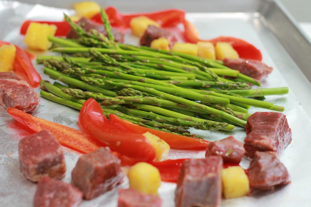 Asparagus, chopped pineapples, sliced red bell peppers, and steak all placed on one pan ready to be cooked.