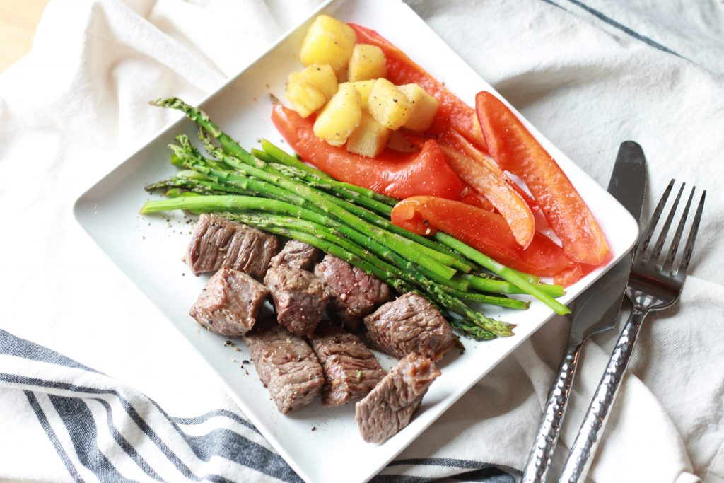 Asparagus, chopped pineapples, sliced red bell peppers, and steak all placed on a white plate ready to be eaten.